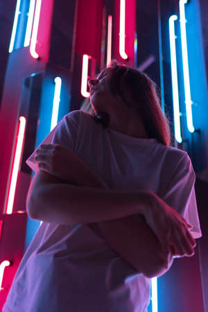 Portrait of a beautiful young woman in cyberspace. Colorful neon lamps