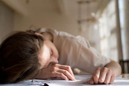 Information overload. The woman sleeps on the documents. Stress and fatigue at work. Bankruptcy analysis