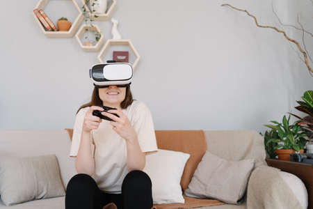 Person plays on the sofa in a virtual reality headset. Cozy light interior