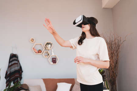 New experience in cyberspace. Slender woman in VR headset touches things in the air in beautiful modern interior