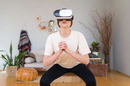 Sport and technology. The gym is at home. Slender woman in virtual reality headset doing exercises at home