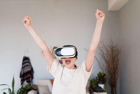 Winner person. Slender woman in virtual reality helmet emotionally celebrates victory