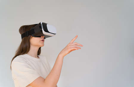 Shopping in cyberspace. Young woman in virtual reality headset chooses gifts on the Internet Imagens