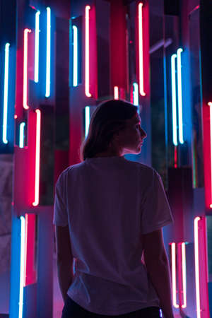 Silhouette of a young woman against the background of bright neon