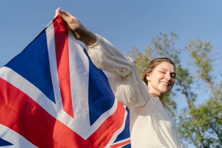 Immigration to Britain. A young adult woman with an English flag is happy and looks at the camera