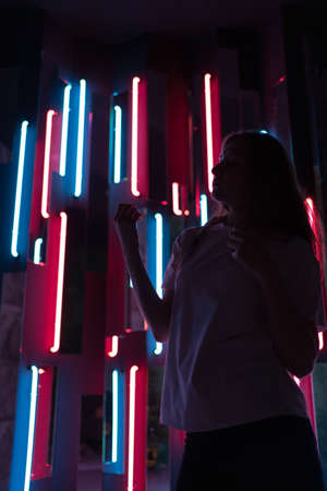 Silhouette of a dancer in a dark neon room, relaxed dancing