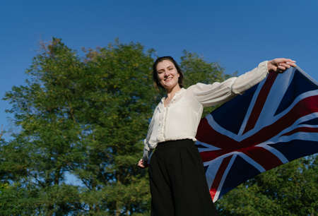 Patriotic young woman with The flag of Great Britain against the background of green tree and blue sky happy and smiling Imagens