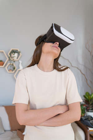 Cyberspace inside the house. Modern young woman in white virtual reality helmet smiles