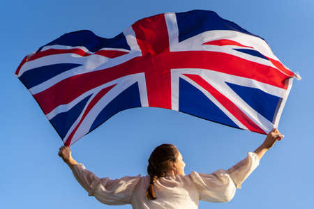 The flag of England waving in the hands of a woman against the blue sky. View from the back. Great Britain, victory and success
