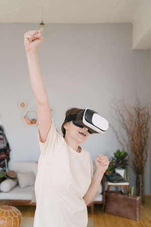 Vertical shoot - An excited young woman celebrates winning in cyberspace. Online competition