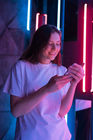 Vertical shot - success and a winner. Amazed young woman in neon lamps Archivio Fotografico
