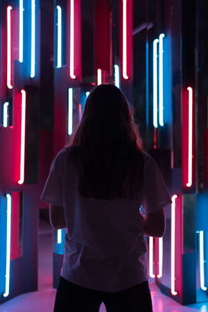 Vertical shot - a view from behind on the silhouette of a woman standing in neon light