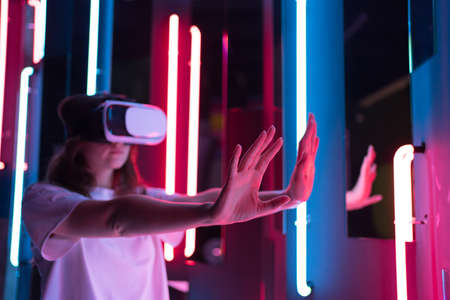 Slender woman in a white virtual reality helmet in cyberspace. Immersive entertainment of the future
