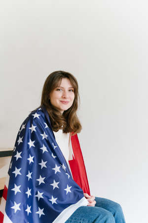 A beautiful American woman with a flag sits on the stairs and smiles at the camera. U.S. National Flag