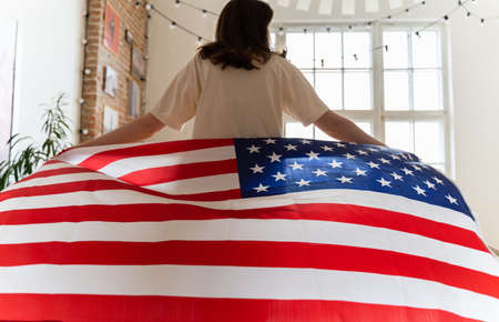 The American flag beautifully waving behind a woman walking into the light. July 4 in the USA