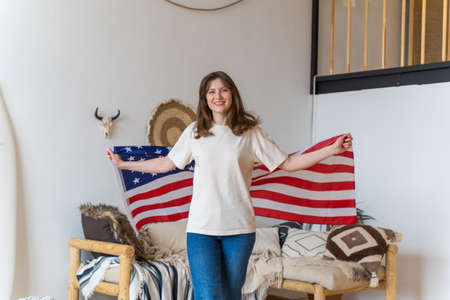 The symbol of America - flag in the hands of a beautiful woman in summer clothes. The person goes and looks into the camera