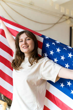 A patriotic woman with a US national flag celebrates, frontview. Independence Day