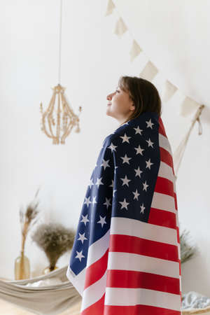 US flag. A proud woman stands with the national flag and looks into the distance. Freedom, democracy and independence