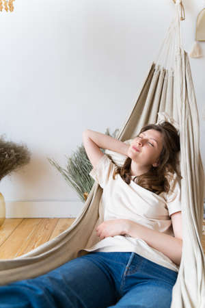 A woman lying in a hammock. Relax on womens day. Life is on pause. Rest after a hard day