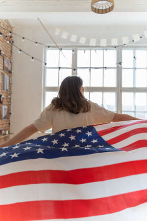 The US flag is waving. The person goes with the national symbol. Patriotic woman