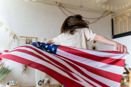 A woman whirls and dances with the American flag. Happy Patriot Archivio Fotografico