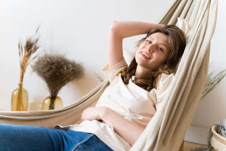 Relaxing in a hammock. A beautiful woman rests quietly and enjoying. break. Positive thinking