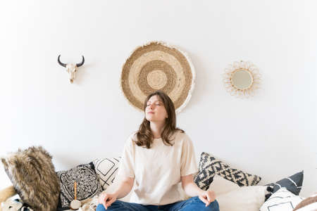 A healthy lifestyle. A woman rests in casual clothes in an authentic room. Lotus pose on the sofa, meditation