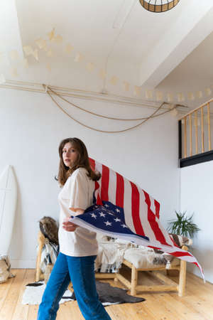 American patriotism. A free and independent woman looks into the camera and walks with the US flag