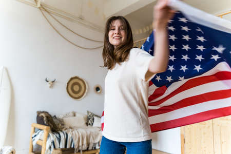 Independence of the US. A woman is whirling with the American flag. National Day