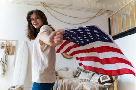 US. Independence and immigration. Beautiful young woman poses with Americas national flag Archivio Fotografico
