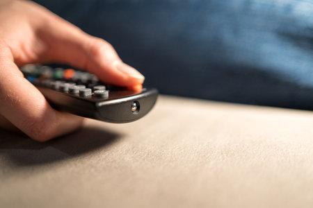Smart TV control. The person presses the remote button close-up