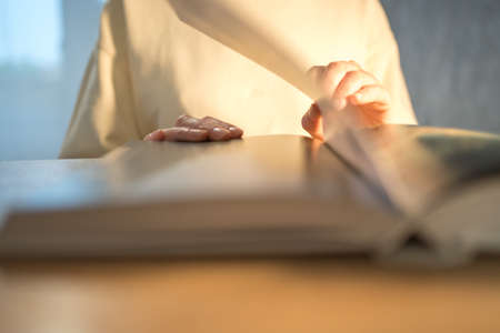 Reading a book. A person flips paper pages close-up
