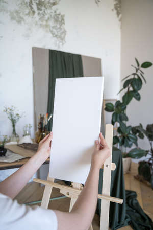 The artist places a white canvas on an easel. Hobbies, drawing. Preparing tools Archivio Fotografico