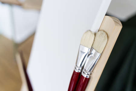Brush for drawing and white canvas on easel close-up
