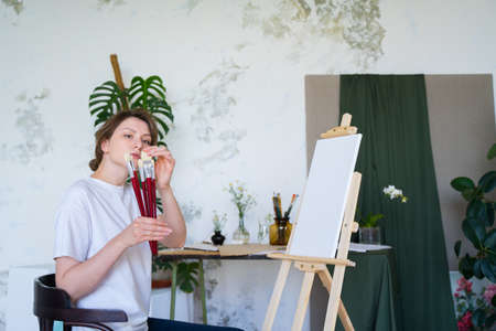 A female artist checks brushes for drawing. Talented painter. Professional creative education