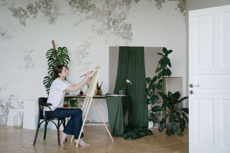 Painter. Creative work. A woman uses imagination and paints a picture in studio