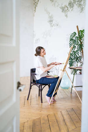 Painter in a workshop. View from the door. Young female artist draws sitting in front of easel