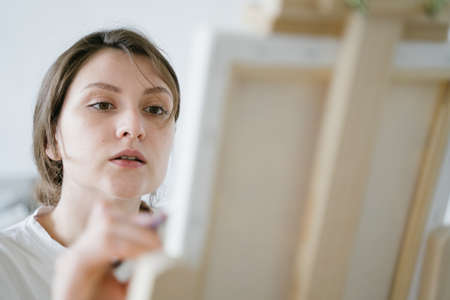The focused face of the artist. Creative process. Talented entrepreneur draws pictures to order