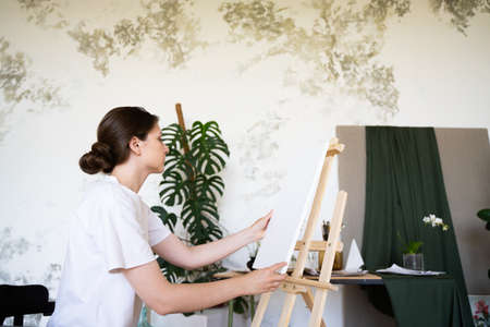 The artist prepares a workplace in a creative workshop. Female painter installs white canvas on wooden easel