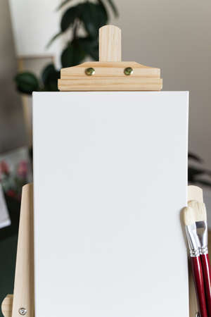 Creative studio. Empty white canvas on a wooden easel and red brushes