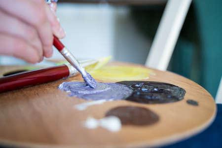 The artist mixes colors on the palette, close-up. Creative loft workshop