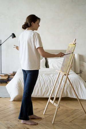 Creative hobby. Inspiration and creativity. A young woman paints a picture Archivio Fotografico
