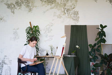 Painter squeezes the paints on the palette. Talented artist works in her studio