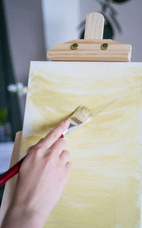 Oil painting. The artist has the idea of drawing. A woman applies yellow paint to a white canvas