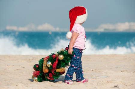 pull toy: niña dibuja un árbol de Navidad en la playa, una niña con un árbol de Navidad en una playa de arena blanca