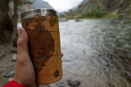 Mug in the hand. Hiking in the mountains