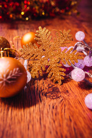 gold christmas balls  and garland on wooden background