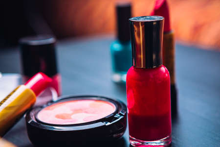 blush cosmetics nail  polish and lipstick on a dark wooden background