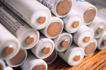 Tops of many AA   white batteries in closeup on wooden background