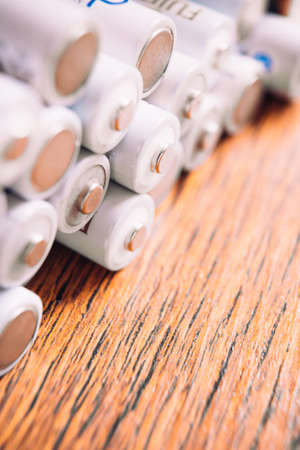 upright row: Tops of many AA   white batteries in closeup on wooden background